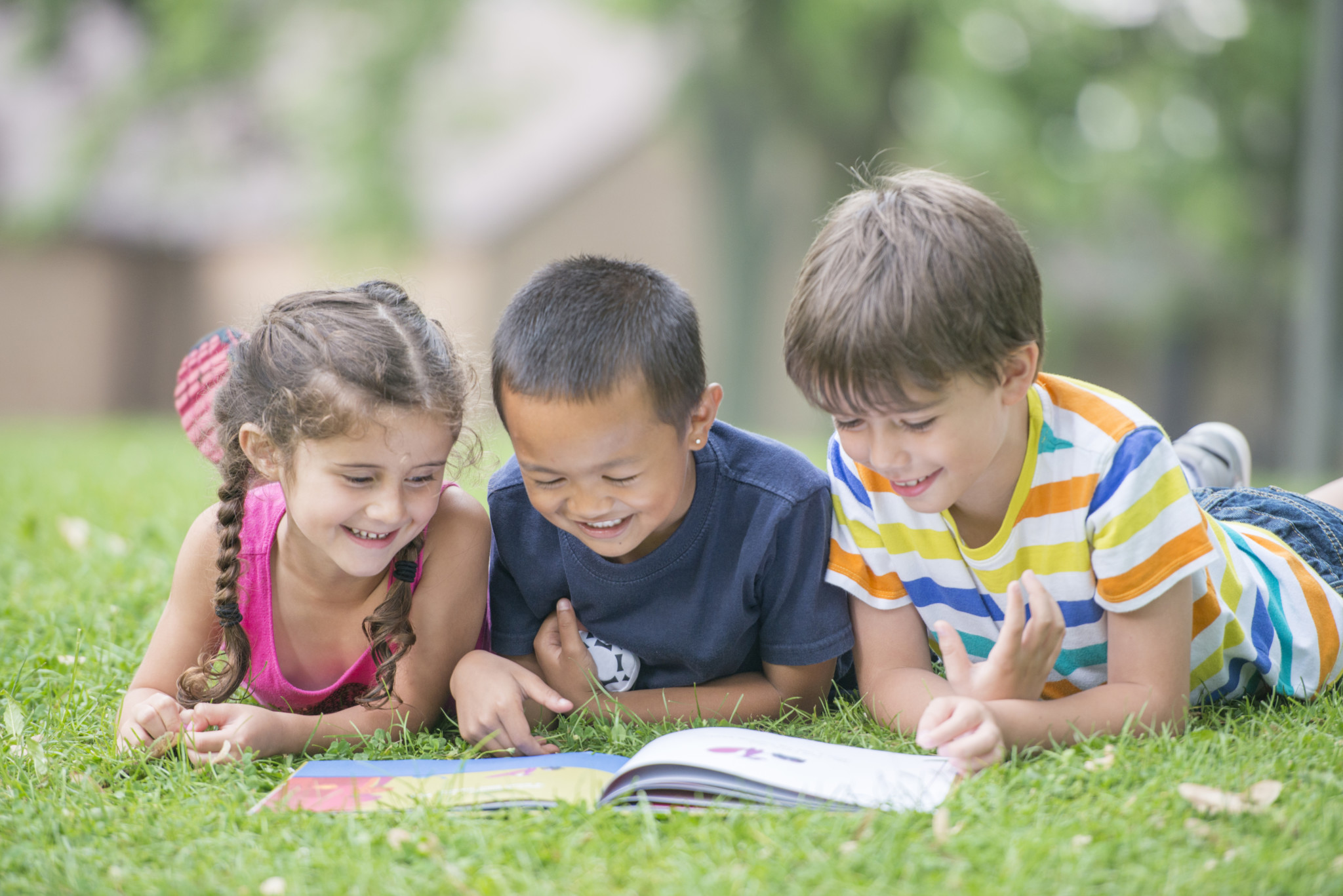 A multi-ethnic group of elementary age children are lying in the grass and are reading a book together in the grass.