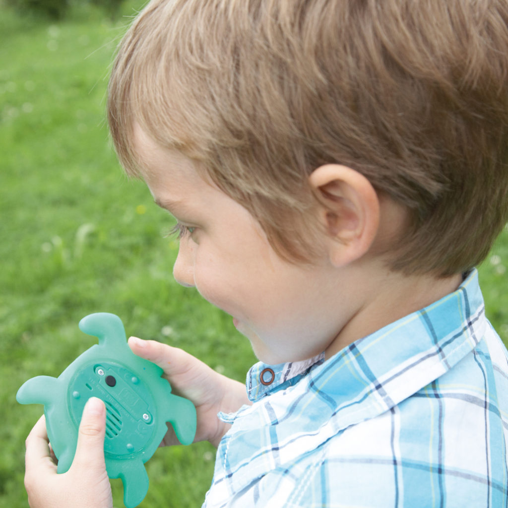 boy talking into a recordable turtle