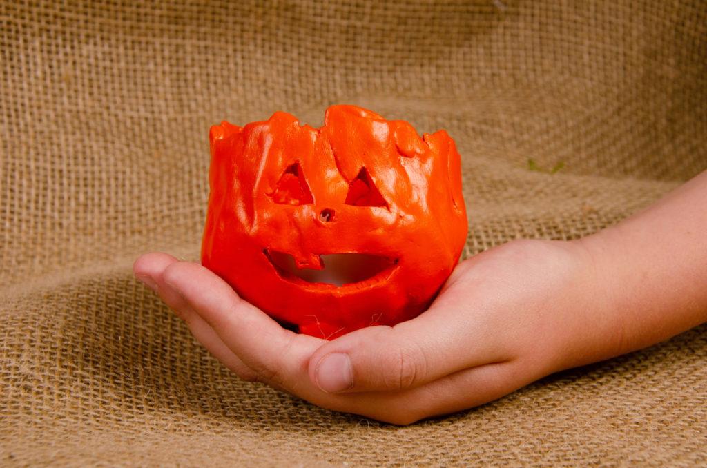 Child holding a small clay pumpkin lantern