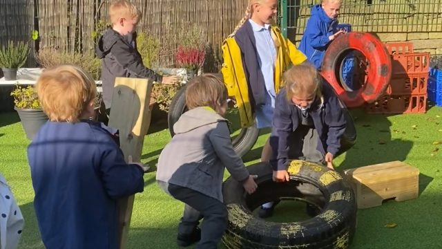 Children work together to lift and move tires and planks.