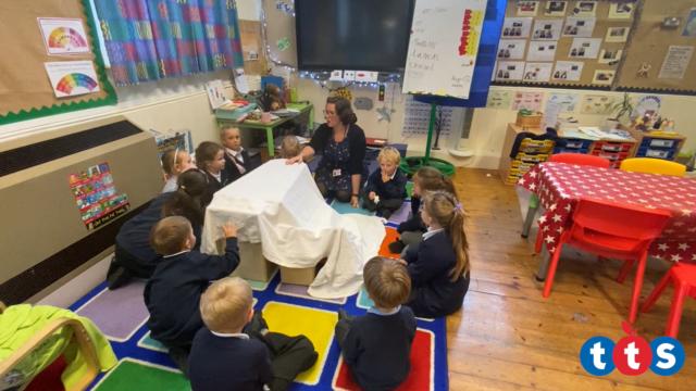 Children wait to see what's under the blanket