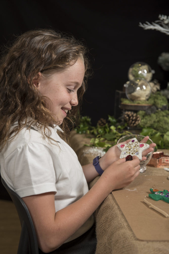 Girl decorating her clay star