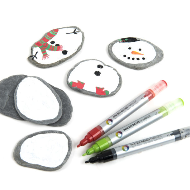 Stones, paint and paint markers for making mix and match snow people.