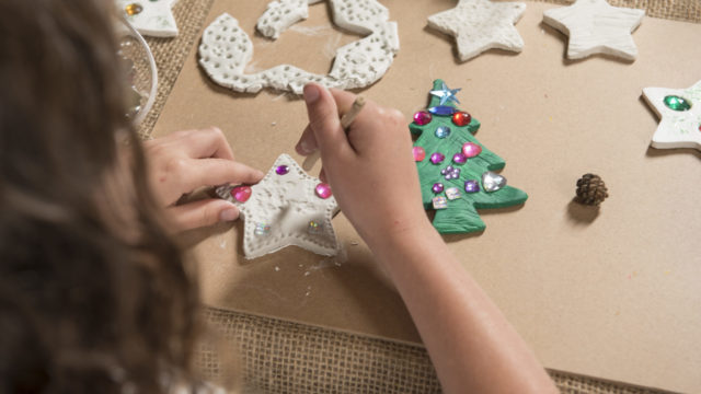 Girl makes patters on clay star