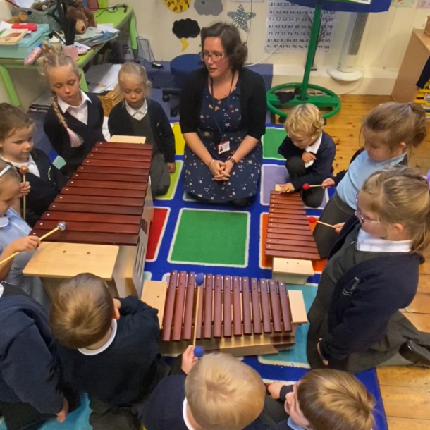 Class of children around three xylophones
